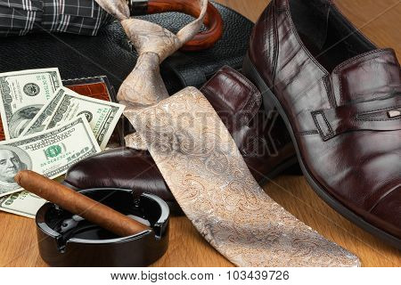 Classic men's shoes, money, tie, umbrella, cigar, ashtray and  bag on the wooden floor
