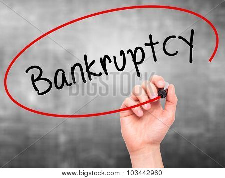 Man Hand writing Bankruptcy with black marker on visual screen.