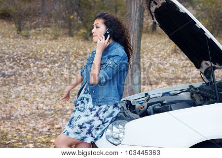 Woman with broken car talk on phone with hood up