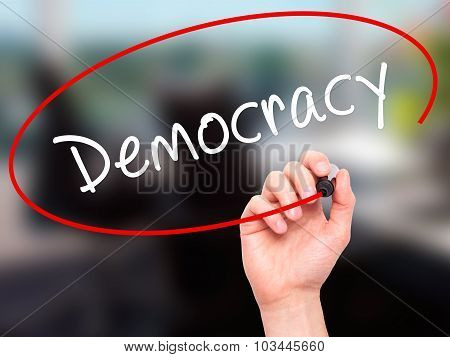 Man Hand writing Democracy with black marker on visual screen.