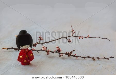 Japanese Kokeshi Doll And   Sprig Of Cherry Blossoms.
