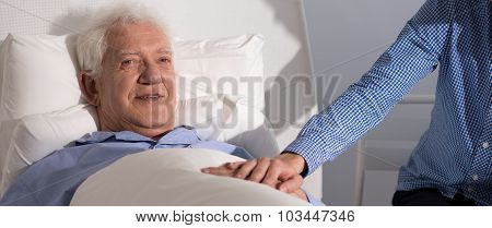 Smiling Grandfather Holding Grandson's Hand