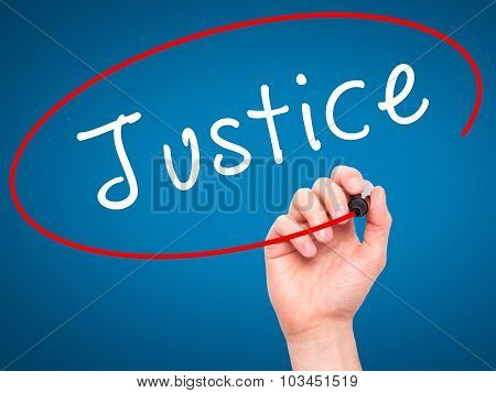 Man Hand writing Justice with black marker on visual screen.