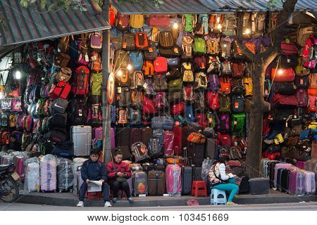 HANOI, VIETNAM, DECEMBER 16, 2014 : A couple is selling a very large choice of bags and suitcases in the streets of Hanoi, Vietnam