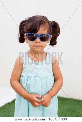 Funny little girl with pigtails and sunglasses outdoor