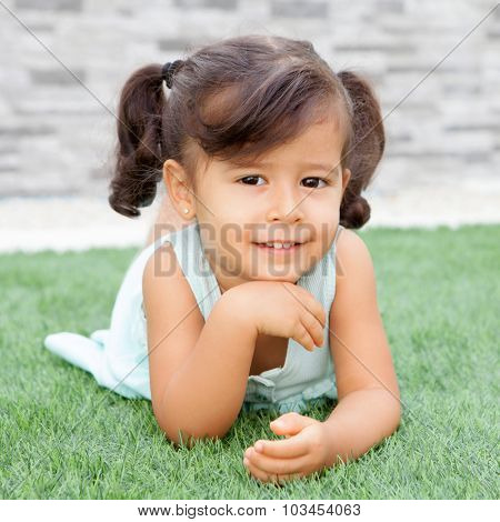 Funny little girl with pigtails lying on the grass