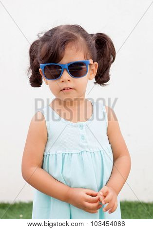 Funny little girl with pigtails and blue dress outdoor