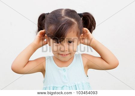 Funny little girl with pigtails making the gesture to hear