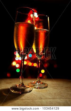 Flutes of champagne on christmas tree bokeh background