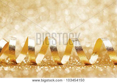 Shiny golden ribbon curls on golden glitters