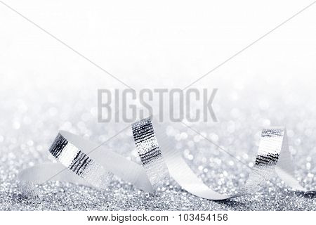 Shiny silver ribbon curls on silver glitters with white copy space