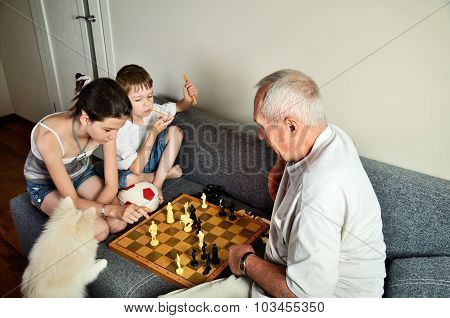Grandchildren With Grandpa Playing Chess