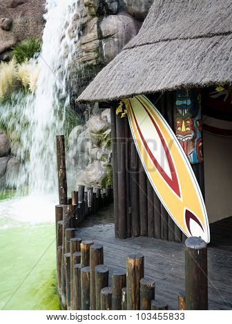 Colorful Surfboard And Typical Hawaiian Hut.