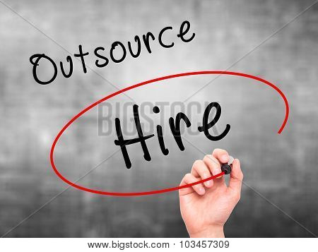 Man Hand writing and Choosing to Hire instead of Outsource with black marker on visual screen.