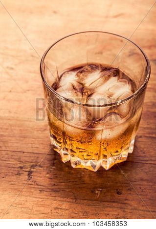 Glass of cold whiskey on wooden surface.