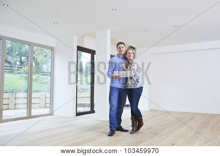Happy Young Couple Looking At Details Of New Home