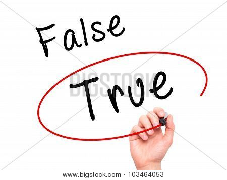 Man Hand writing an choosing True instead of False with black marker on visual screen.