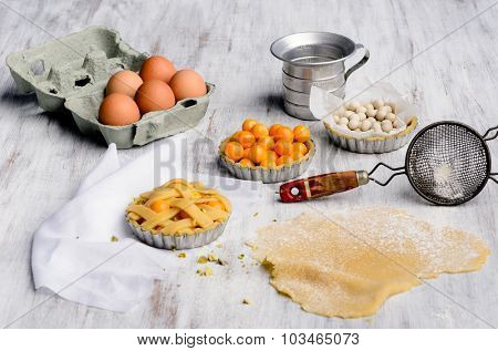 Raw elements of tart making baking process with dough, fruit, tins, beans, flour and vintage baking utensils