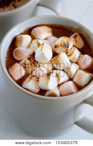 Close up of hot chocolate cocoa drink, comforting cozy delicious topped with roasted toasted marshmallows
