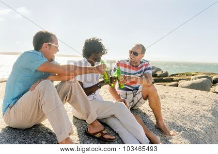 Friends hanging out by the beach drinking beers, enjoying the sunny afternoon