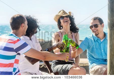 Friends toasting drinks at the beach party on a sunny afternoon, having fun on holiday