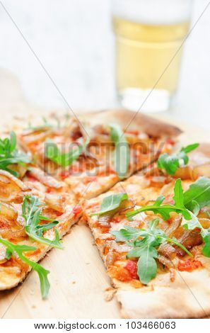 Pizza topped with tomato, caramelised onion and fresh rocket, fresh handmade thin crust and beer