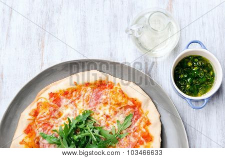 Whole pizza with salami, melted mozzarella cheese and fresh rocket from overhead