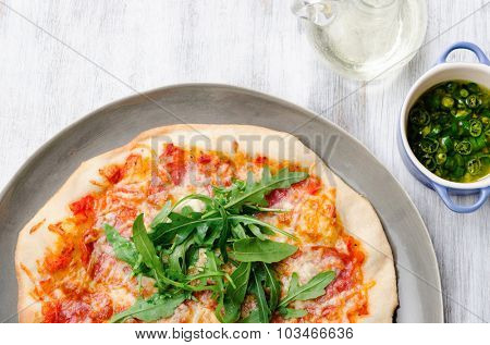Pizza with salami and cheese topped with wild rocket from overhead, rustic gourmet thin crust