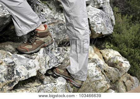 Side view of a pair of hiking boots worn by a person climbing up a rock face