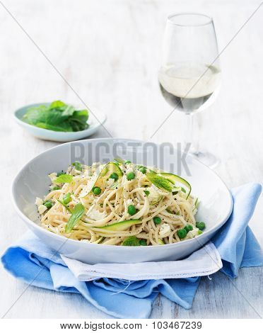 Healthy meal, spaghetti pasta with feta cheese, shredded zucchini, green peas, olive oil and mint