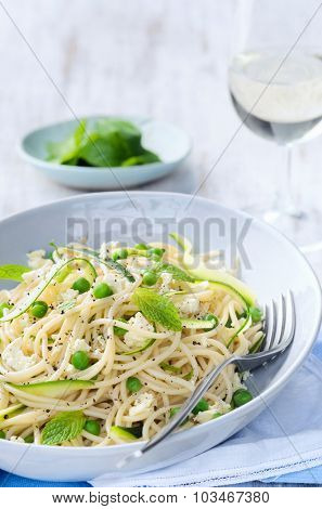 Healthy green pasta with fresh peas, zucchini and mint leaves