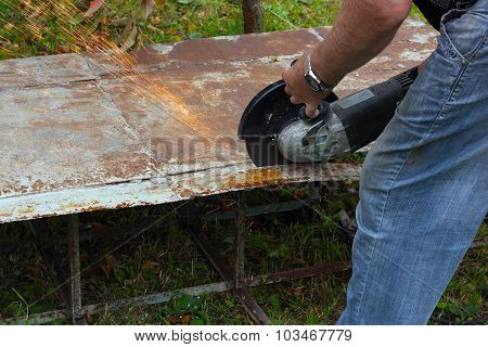 Worker Cuts Metal Sheet By Angle Grinder