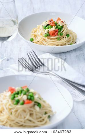 Bowls of delicious pasta topped with cherry tomatoes, peas and feta cheese