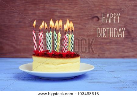 the text happy birthday and a cheesecake with some lighted birthday candles of different colors, on a rustic blue wooden table