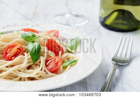 Spaghetti pasta meal with cherry tomatoes and basil, accompanied by white wine