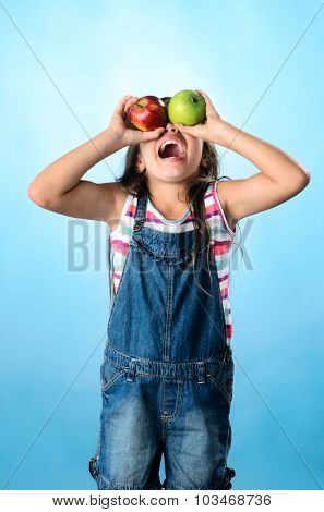 Portrait of young playful kid covering her eyes with red and green apple, healthy eating concept