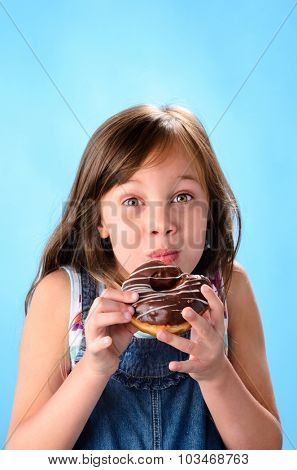 Sweet cute girl eating and enjoying a chocolate glazed donut , on blue background