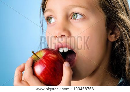 Portrait of a young girl biting into a red apple
