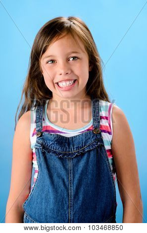 Happy young school girl in denim dungarees cute smiling happy portrait