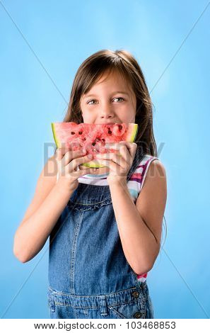 Cute young kid eating a slice of red juicy watermelon