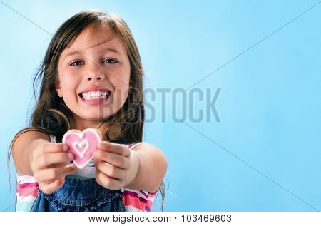 Happy smiling adorable young girl in denim dungarees holds out a pink heart shape cookie, valentines or mothers day concept