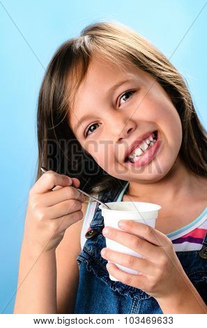 Close up of young girl eating healthy food plain yoghurt