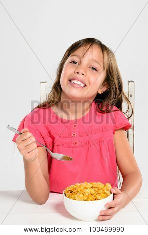 Happy healthy school girl eating a bowl of cornflakes cereal, starting the day right with a well-balanced breakfast