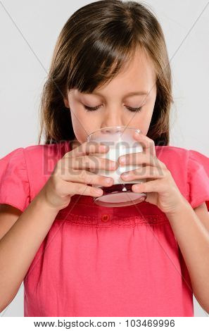 Cute adorable girl holding a glass of milk, part of a healthy nutritious diet