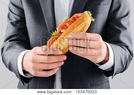 Man in business suit holding a take away lunch sandwich baguette, hands only