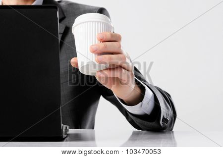 Man in business suit working on his laptop computer and drinking coffee from a take away disposable cup