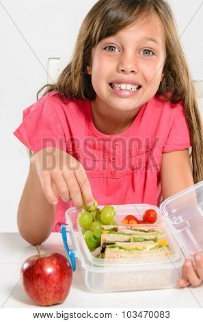 Happy smiling school girl with healthy lunchbox filled with fresh fruit and sandwich
