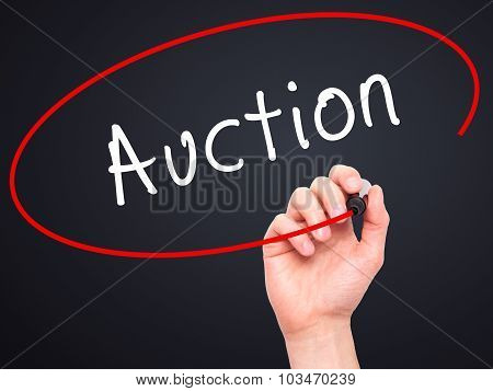 Man Hand writing Auction with black marker on visual screen.