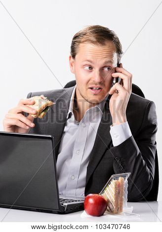 Busy hardworking business man eats lunch at his desk while working and talking on his mobile cell phone