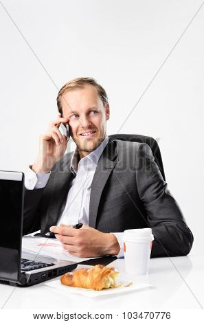 Man in business suit talks on mobile cell phone while drinking coffee and eating croissant pastry at his desk with laptop and documents